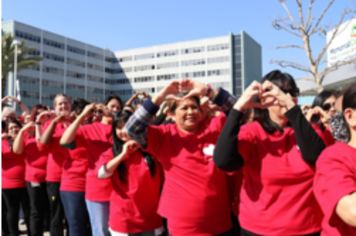 Long Beach Medical Center employees wearing red tee shirts make heart shape with their hands