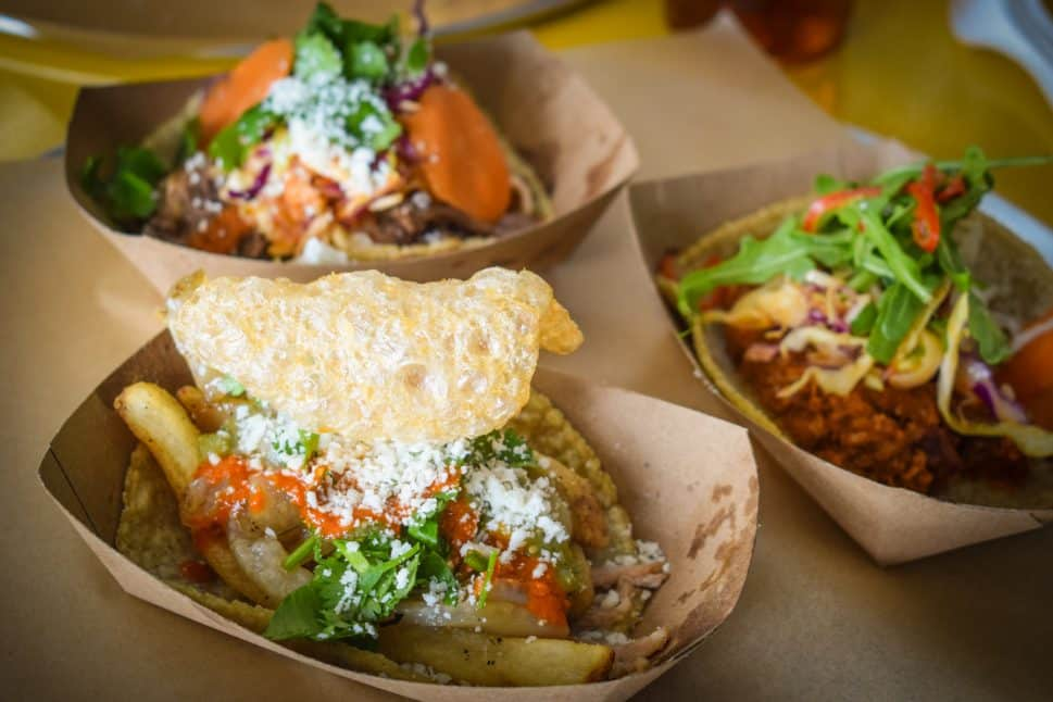 Three different tacos sit in individual paper trays.