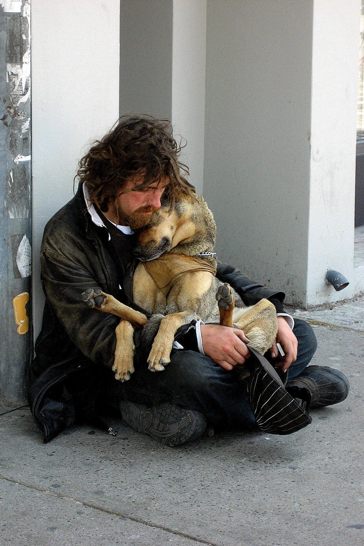 homeless man with longish brown hair and beard in old clothing sits on street closely cuddlinghis large tan-and-gray dog
