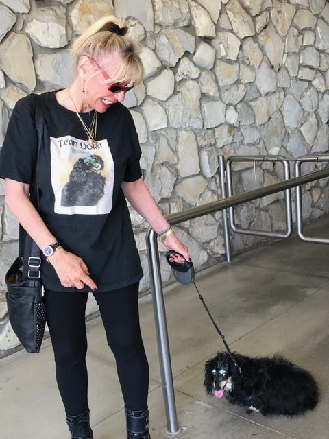 Woman with blond hair in a bun, a T-shirt with Princiess Dora on it, and black jeans with a black-and-white dachshund on least.