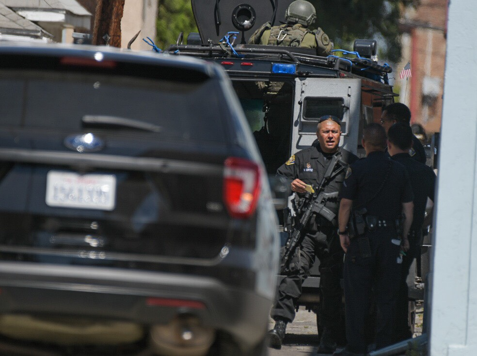 SWAT officers surround a building near where a woman was found shot to death Thursday, July 11, 2019. Photo by Thomas Cordova.
