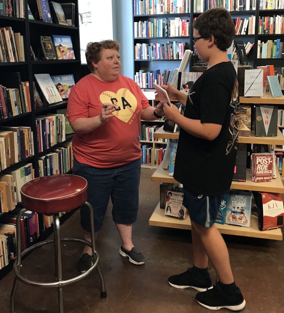short woman with red hair wearing a red T-shirt with yellow logo and black Bermuda shorts talks with a young boy with glasses, a black T-shirt and plaid shorts. They're surrounded by shelves of books.