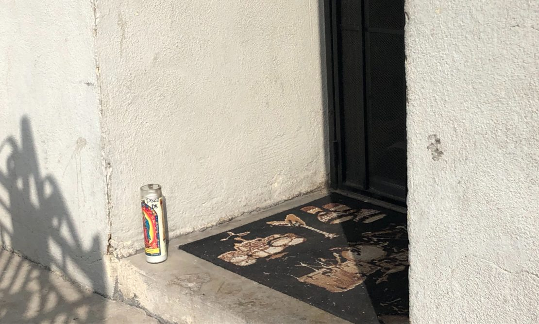A candle at the door of an apartment where the shooting happened on Linden Avenue near 60th Street on Oct. 13, 2019. Photo by Stephanie Rivera.