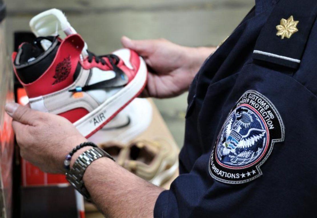 A customs agent with one of the seized counterfeit Nike shoes. Photo courtesy CBP.