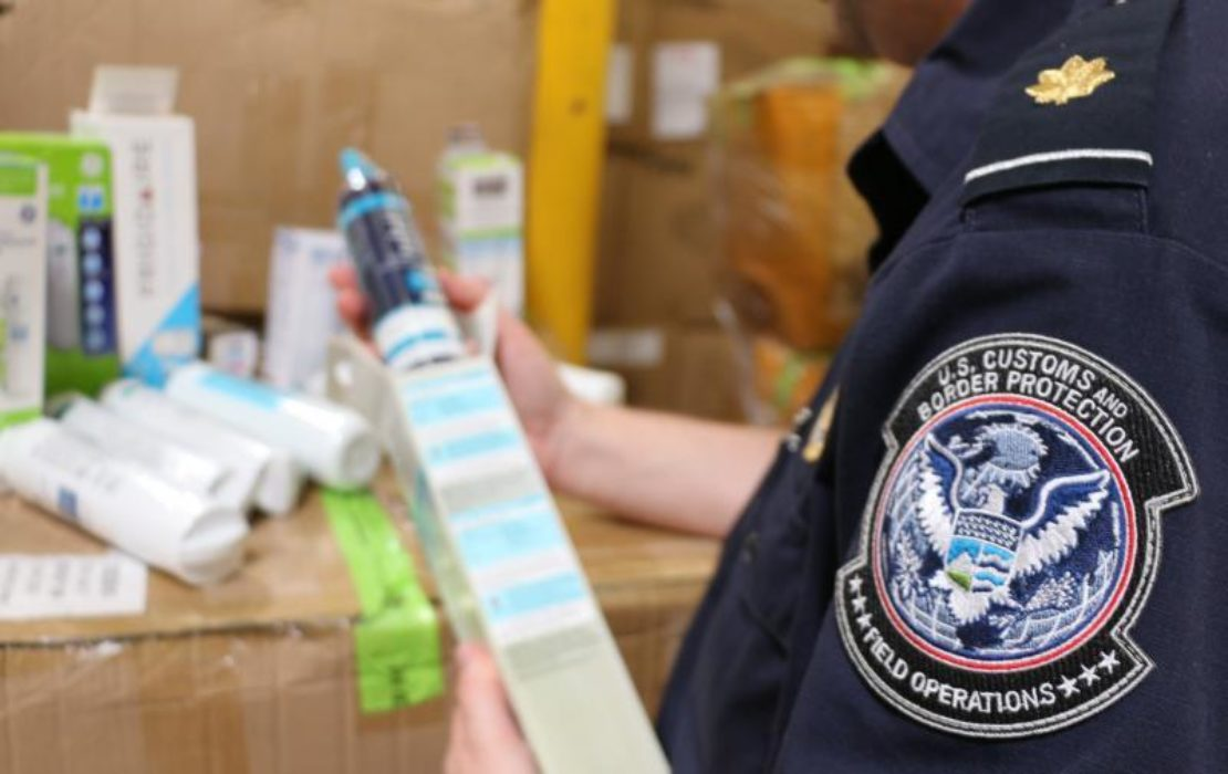 An agent inspects the counterfeit items. Photo courtesy CBP.