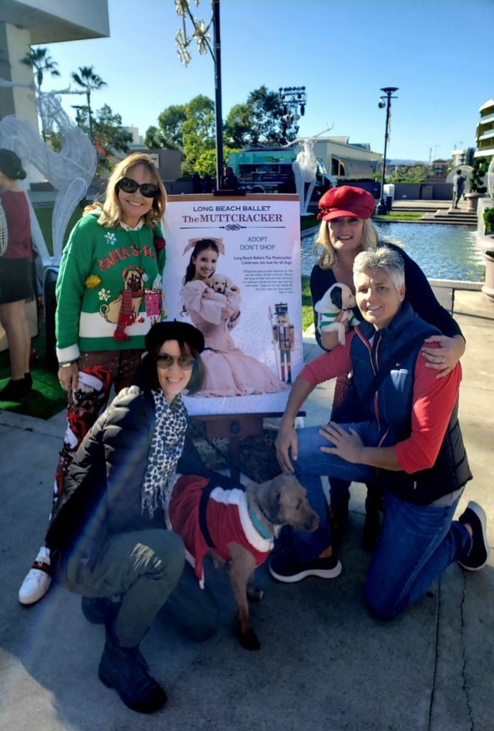 Four women in Christmas sweaters and bright hats surround a Nutcracker poster