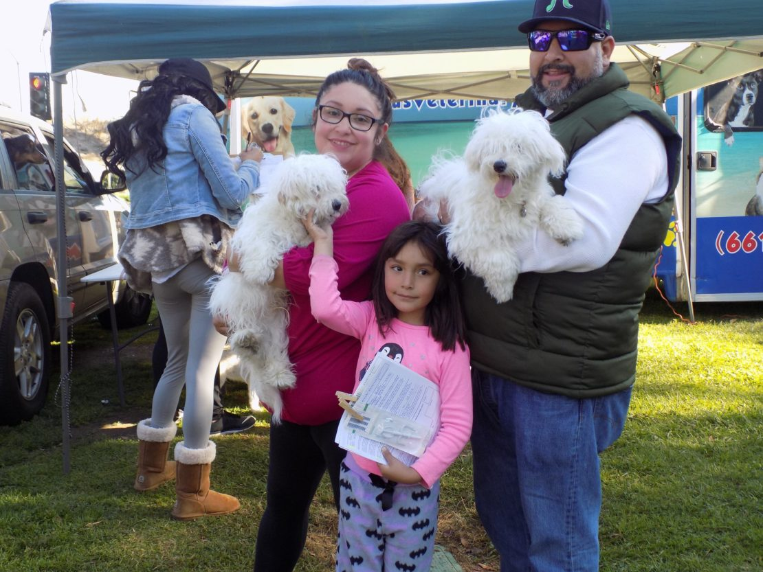 FAmily --mother, father, and little girl carry two fluffy dogs