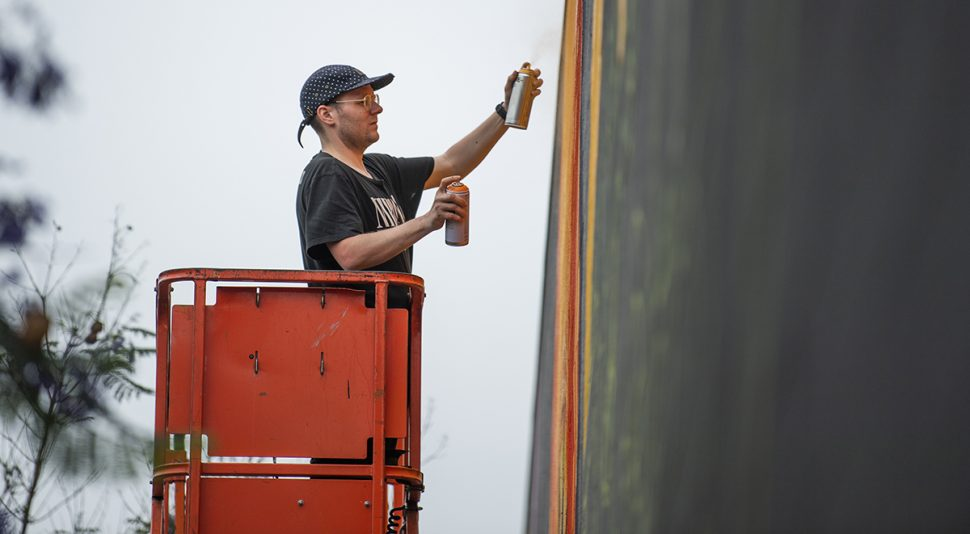 Peter Robinson of Seattle, who goes by his artist name Ten Hundred paint a large-scale mural at the SteelCraft parking lot at Bixby Knolls in Long Beach June 21, 2018. Robinson has murals in Seattle, New York City, Los Angeles, Kansas City, Tokyo Japan and Buzios Brazil. Photo by Thomas R Cordova