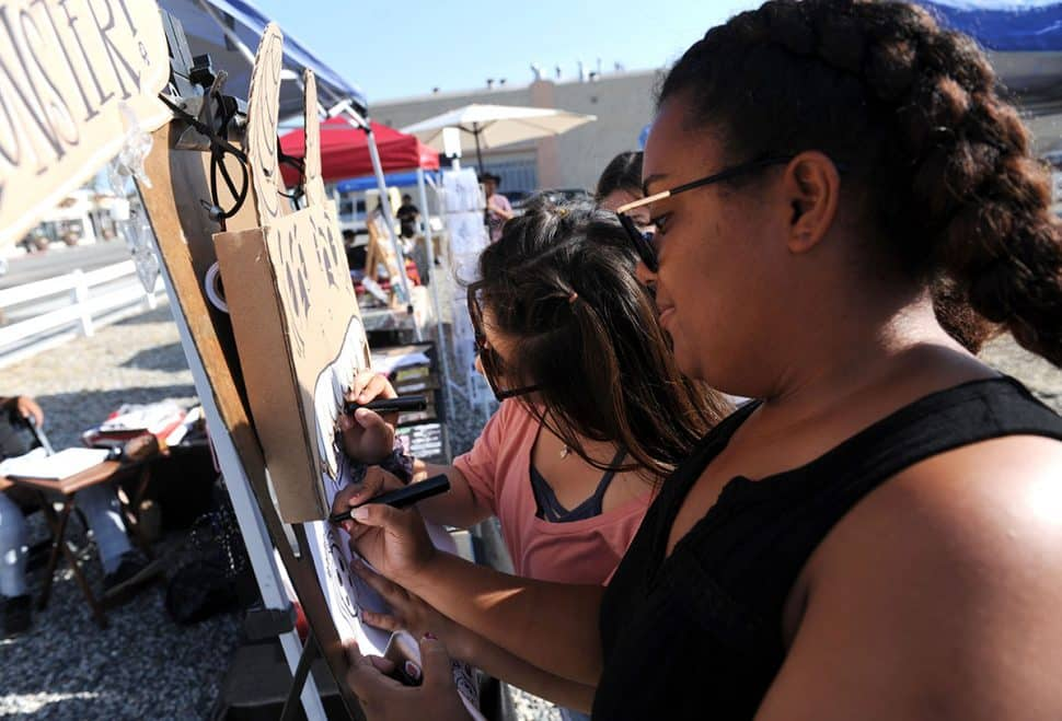 Genesis Valzivia,left, and her friend Amanda Baptist draw charchters during Summer LuvinÕ Fest, at 5301 Long Beach Boulevard in North Long Beach Saturday. The free family friendly event featured multiple bands, as well as vendors, artists and the Long Beach local El Exclusivo food truck on site in Long Beach Saturday, September 1, 2018.<br /> Photo by Stephen Carr / For The Long Beach Post