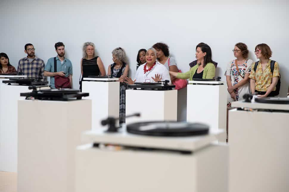 Catherine Scott cries and asks the audience to make a difference after lauren woods puts her art installation, American MONUMENT, on pause until Kimberli Meyer, former art director of the University Art Museum, gets justice at the University Art Museum in Long Beach, Sunday, September 16, 2018. Photo by Kelly Smiley