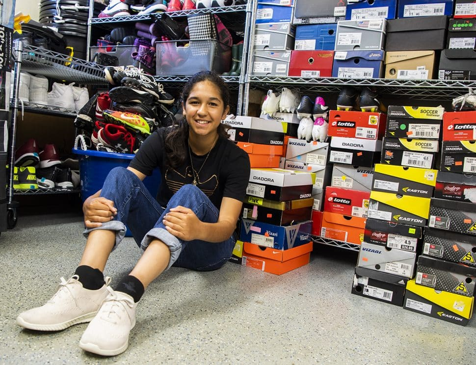 Lily Rodriguez, 14, in a space where His Little Feet keeps its donated shoes. Photo by Thomas R. Cordova.