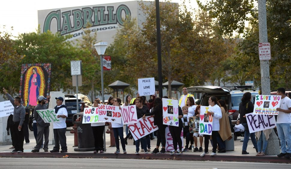 Friends and family gather in front of Admiral Kidd Park along Santa Fe Avenue for a vigil Friday evening for 69-year-old Jose Raul Corrales, who was shot and killed Tuesday afternoon in a drive-by, while watering his front yard near the corner of Summit Street and Canal Avenue, on Friday Oct. 12, 2018. Photo by Stephen Carr.