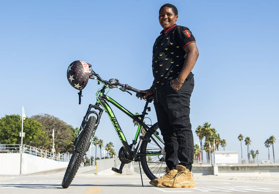 Jassiah Smith,14 of Long Beach, stands next to his new bike after the Long Beach police took a collecting to replace his bike after it was stolen over the weekend in Long Beach October 23, 2018. Photo by Thomas R Cordova.