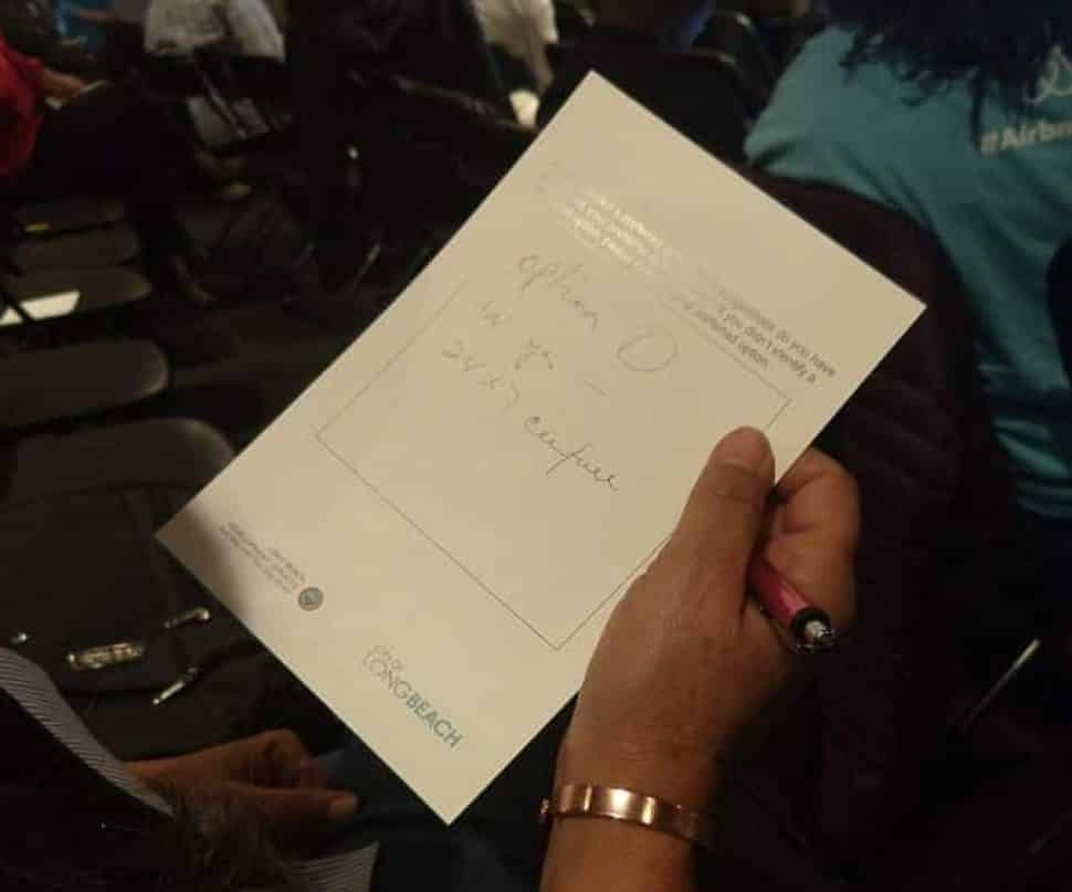 """Emma Valenzuela, a short-term rental host, shows her comment card stating she would rather have """"option zero"""" or no regulations on short-term rentals at a community meeting on Oct. 10, 2018. Photo by Valerie Osier."""