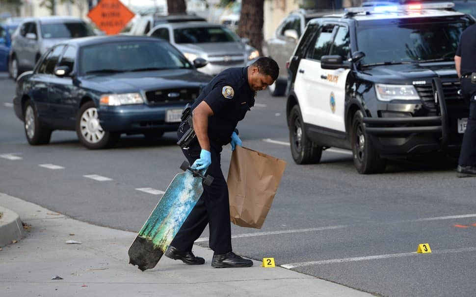 Long Beach Police take a broken skateboard and a shoe into evidence, at the scene of a crash, where a skateboarder was struck by a vehicle at the intersection of Bellflower Boulevard and 27th Street Tuesday. Nov. 27, 2018. Photo by Stephen Carr.