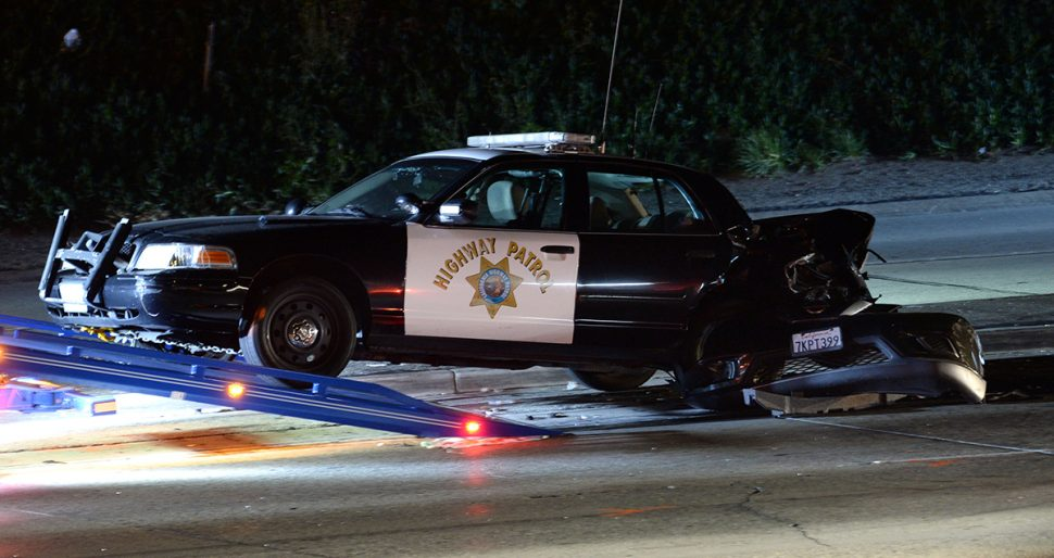 A damaged California Highway Patrol car is towed after it was involved in a collision along the southbound  405 Freeway, between Orange Avenue and Walnut Avenue Saturday night.   Photo by Stephen Carr / For the Long Beach Post