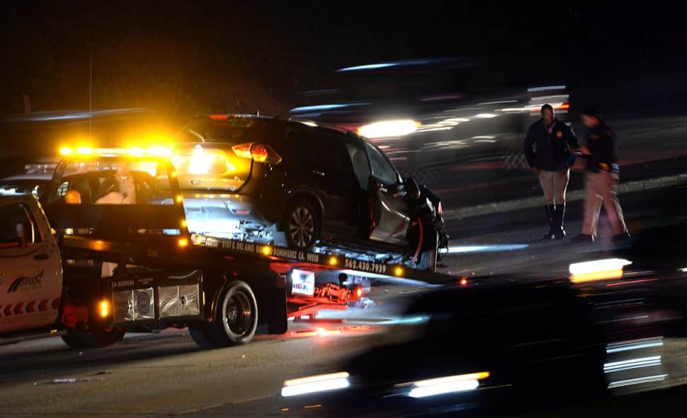 A a damaged SUV along with a damaged California Highway Patrol car are towed after both appeared to be involved in a collision along the southbound  405 Freeway, between Orange Avenue and Walnut Avenue Saturday night.   Photo by Stephen Carr / For the Long Beach Post