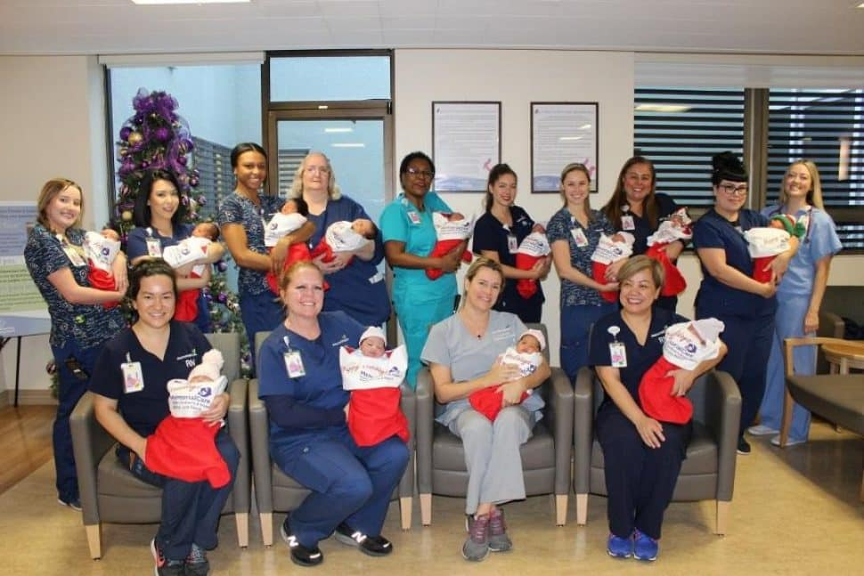 Newborns adorn giant, red Christmas stockings, held by Miller Children's & Women's nurses, in celebration of the upcoming holiday.