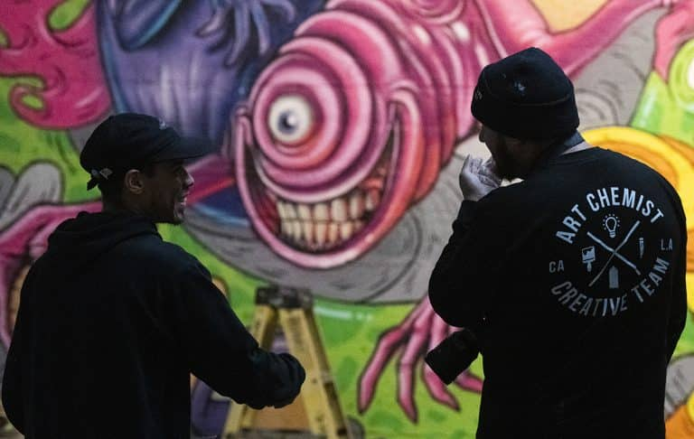 "Edrok-One (left) and Jaime Guerrero (right) both of Los Angeles, talk about Edrok-One's wall piece on Jan. 7, 2019. The group will be displaying their murals and artwork at the Icehouse Arts Complex as part of ""Hello, Welcome"" starting this weekend. Photo by Thomas R. Cordova."