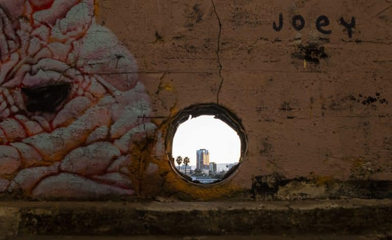 "The Landmark Square building is seen through a hole in the wall from the Icehouse Arts Complex. Muralists will be showing their work during ""Hello, Welcome"" starting this weekend. Photo by Thomas R. Cordova."