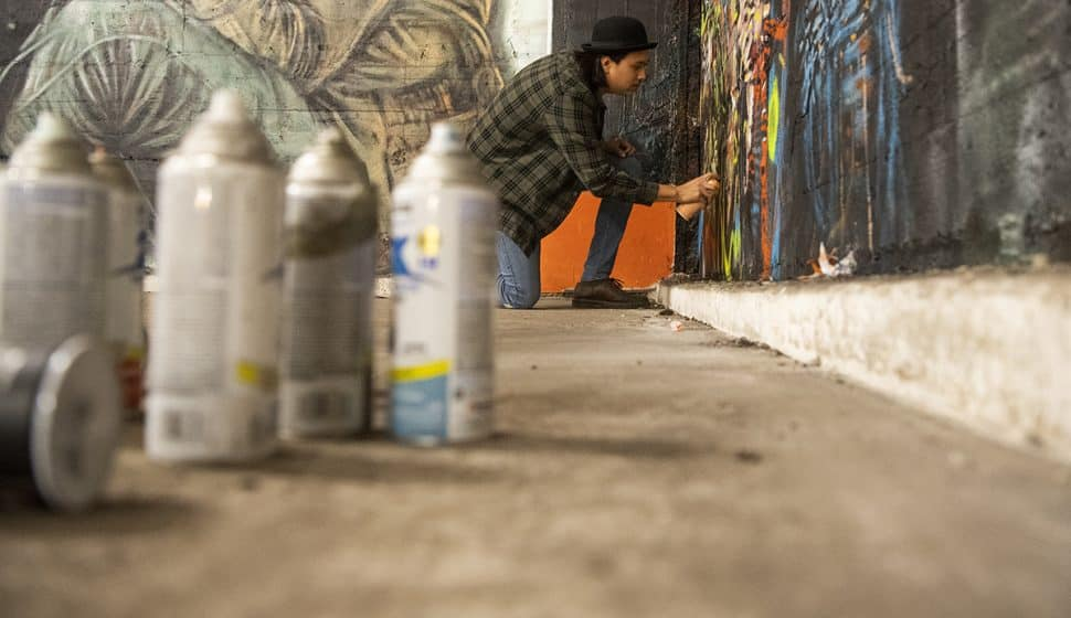 "Kimo Bautista, of Lynwood, uses spray paint for his mural at the Icehouse Arts Complex on Jan. 7, 2019. The group will be displaying their murals and artwork during ""Hello, Welcome"" starting this weekend. Photo by Thomas R. Cordova."