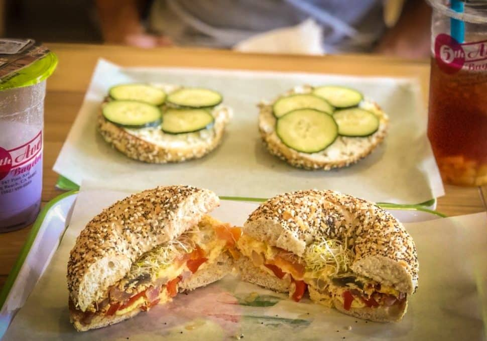 Two plates with bagels; one as a breakfast sandwich and the other covered with cream cheese and cucumbers. Two drinks flank each side.