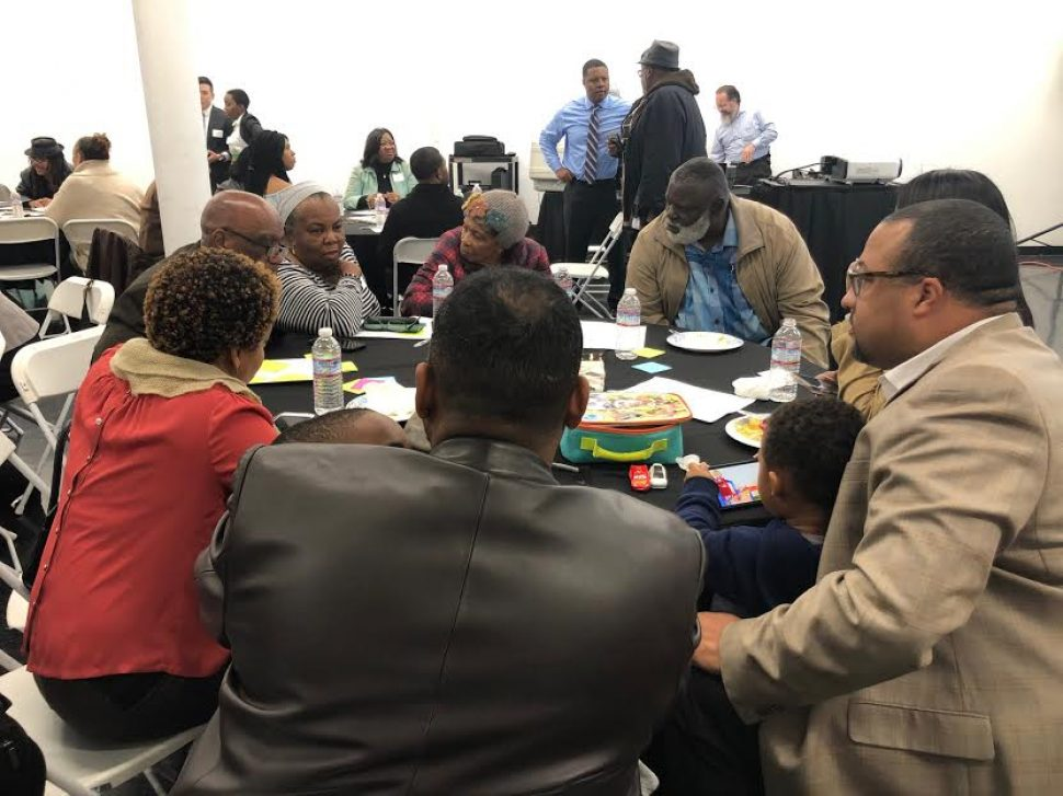 A group of about 10 people gather at a table to discuss ideas for a proposed African American Cultural Center.