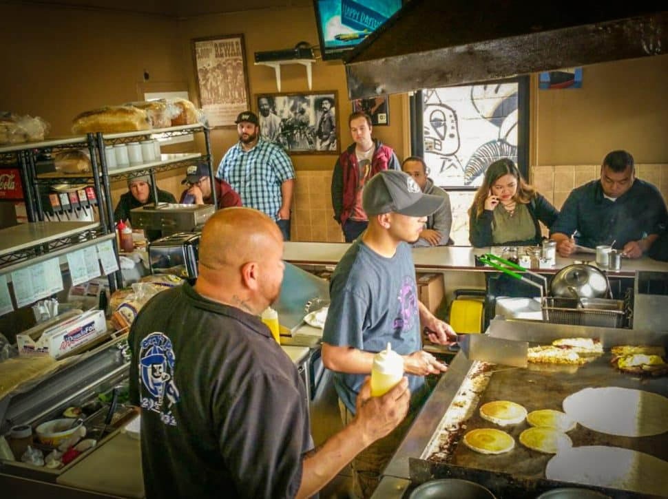 Two cooks stand a griddle inside a small restaurant space surrounded by customers.