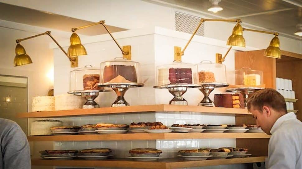 White interior of a bakery and restaurant has open-air shelves lined with various cakes and pies.