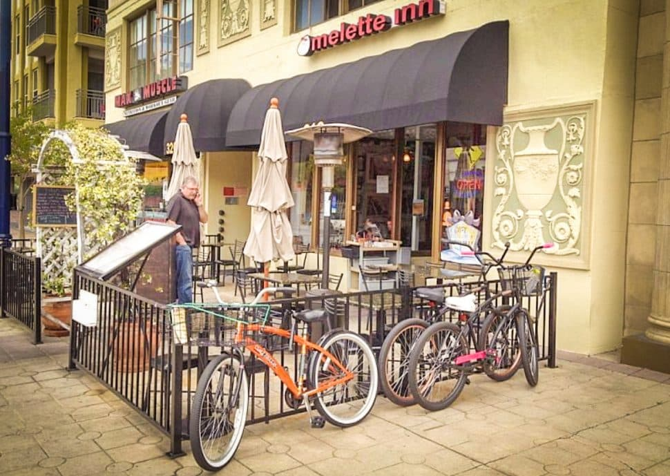 Patio space of restaurant is fenced with bikes locked to it and empty tables.
