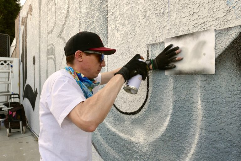 """Artist J. Blanks, known as """"Howdy Y'all"""" works on the 'LBC' of the mural paying homage to music producer Tito Rodriguez. Saturday, Jan. 26. Photo by Asia Morris."""