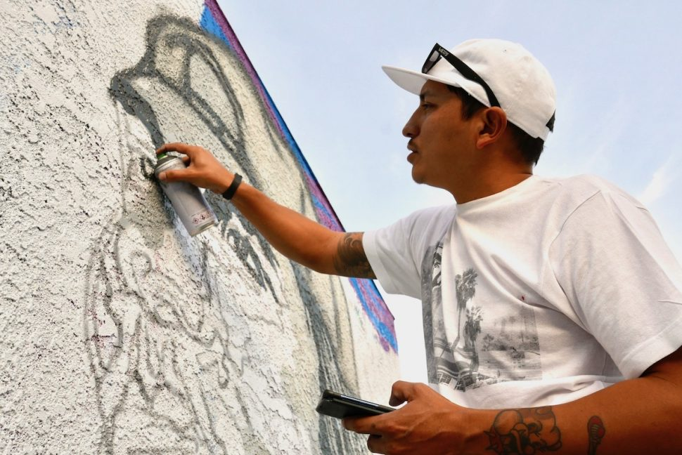 Local artist Erick Guadarrama works on his mural of Long Beach native and music producer Tito Rodriguez at i-nhale Smoke Shop. Saturday, Jan. 26. Photo by Asia Morris.