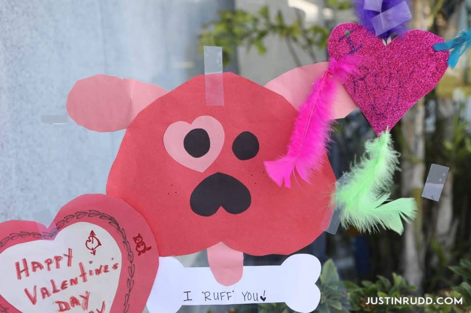 "Valentine card made of heart shapes and shaped into a dog with pink ears, an upside-down red heart face, two black eyes with a pink heart-shaped patch over one, a black upside down heart nose, a pink tongue, and a white bone with ""I love you"" written in ink."