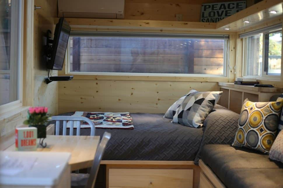 The Tiny House's sleeping space includes a queen size bed with a brown bedspread.