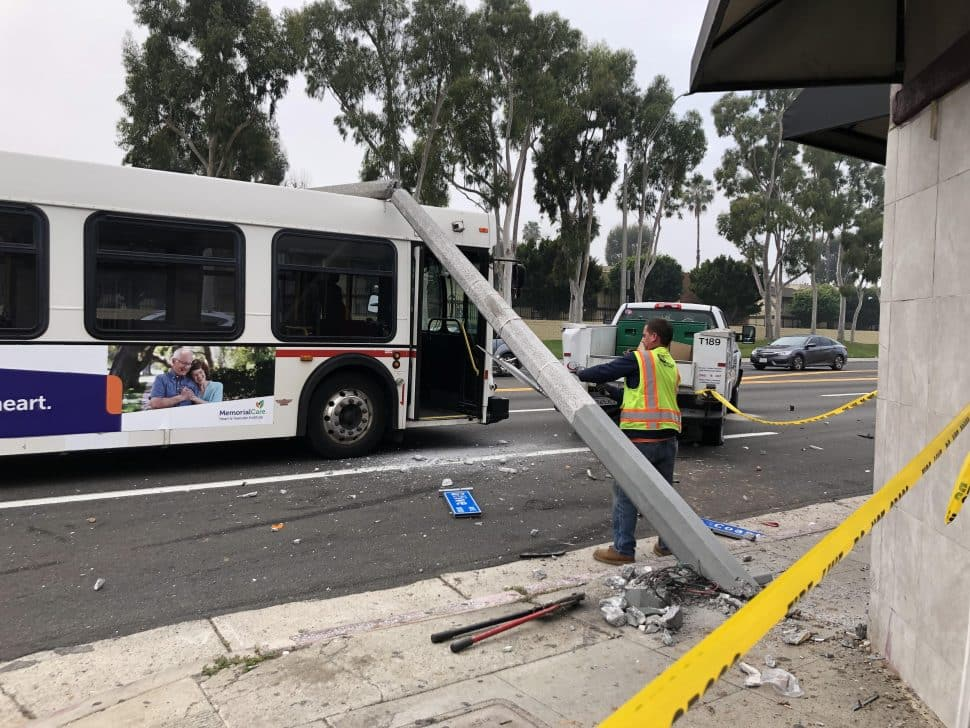 A worker removes the street signs from the light pole perched on top of the bus after a crash at PCH and Olive on Jan. 29, 2019. Photo by Jeremiah Dobruck.