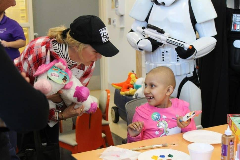 A young patient at Miller Children's & Women's is thrilled to be surprised witha stuffed animal by Liset Meruelo.