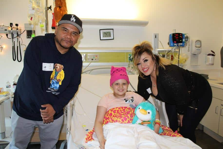 Power 106's, DJs J Cruz and Cece Valencia visit Kayla, 10, at her bedside  to surprise her with a stuffed animal.