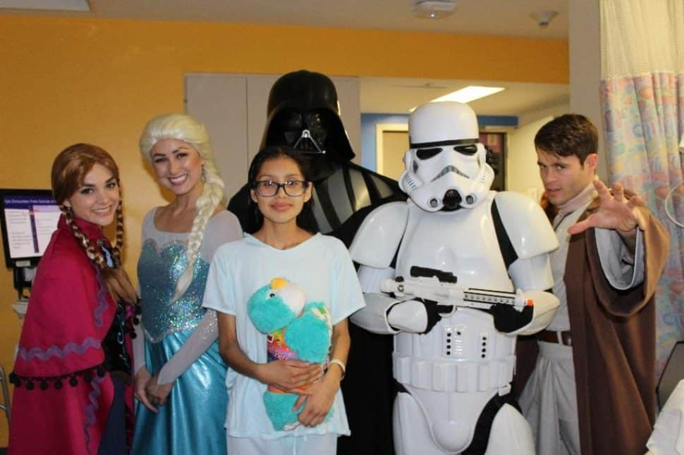 Frozen and Star Wars characters visit and deliver a stuffed animal at a Miller Children's & Women's patient's bedside.