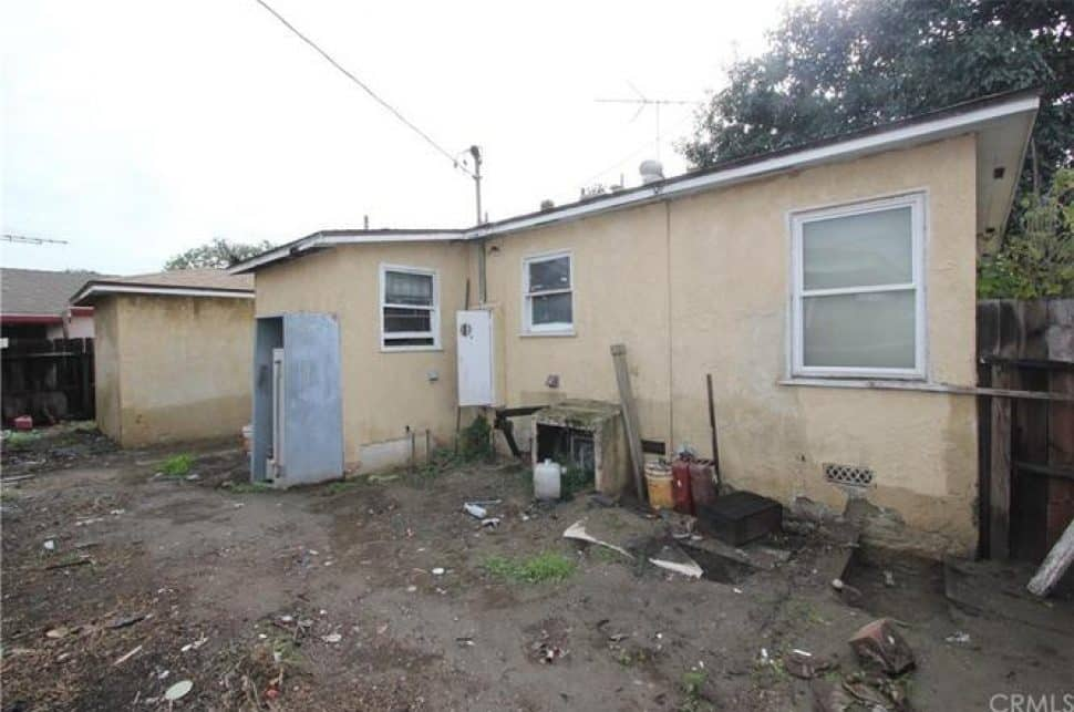 The back of a light brown, run-down home that needs a lot of work