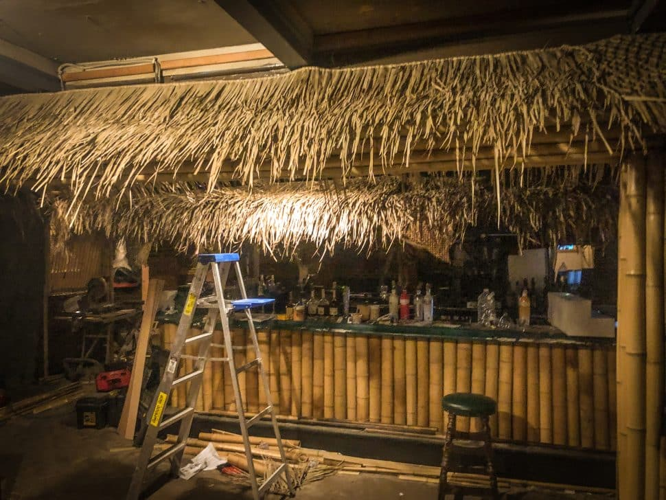 A large bar is being decorated to resemble a beach hut bar with bamboo and leaves.