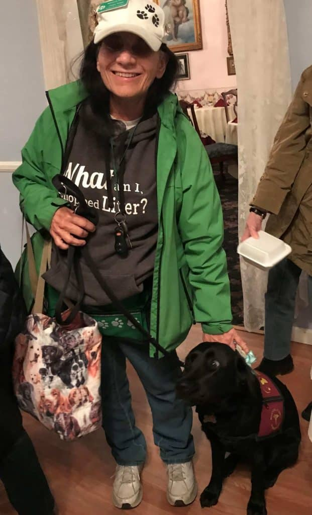 """Woman with dark hair in green jacket and a black T-shirt with the logo """"What am I, chopped liver?"""" stands next to her helper dog, a black lab in a red jacket. Another person stands next to her; you can only see an arm."""