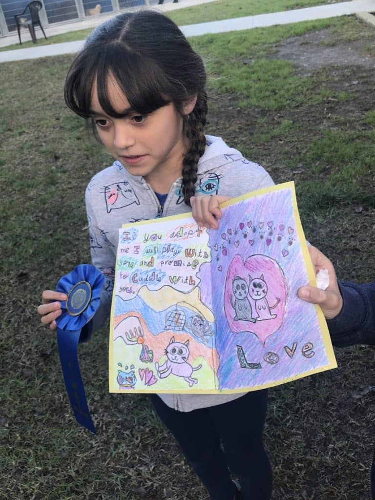"""Little girl with braids and a cat-patterned jacked holds a Valentine card with the message """"If you adopt me, I will play with you and promise to cuddle with you. A pink cat plays near the fishbowl, where three droplets of water are splashing out. Another cat frolics near a birdcage!"""