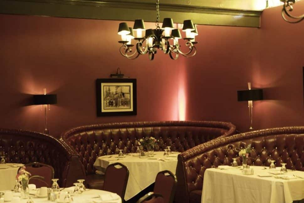 a dining room with red walls and red leather booths