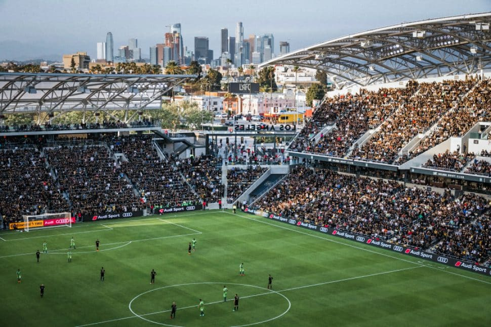 The buildings of Downtown LA act as a backdrop to a giant stadium filled with people watching a soccer game.