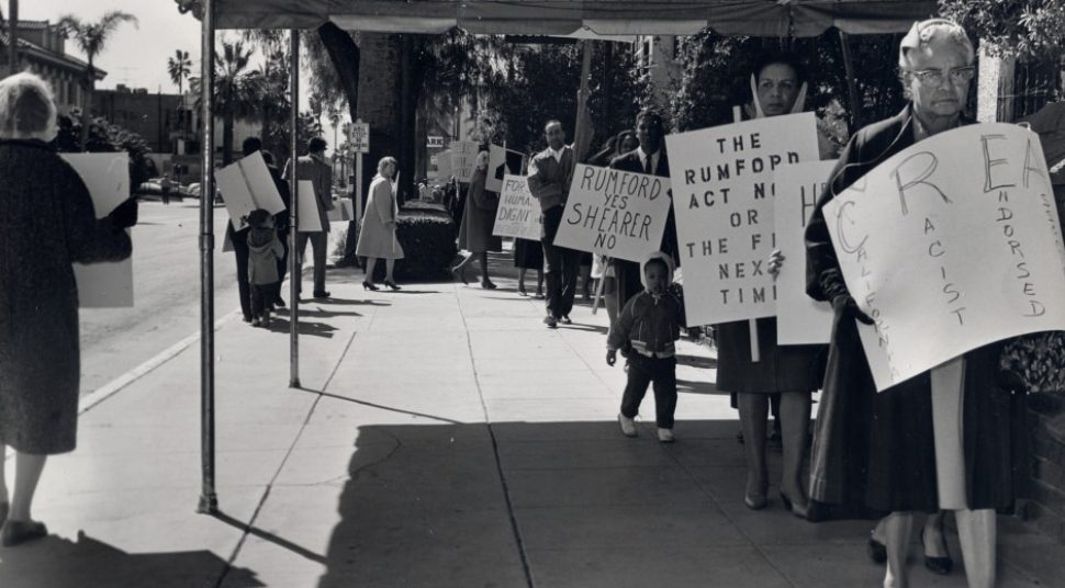 A black-and-white picture shows people marching with protest signs against Prop. 14.