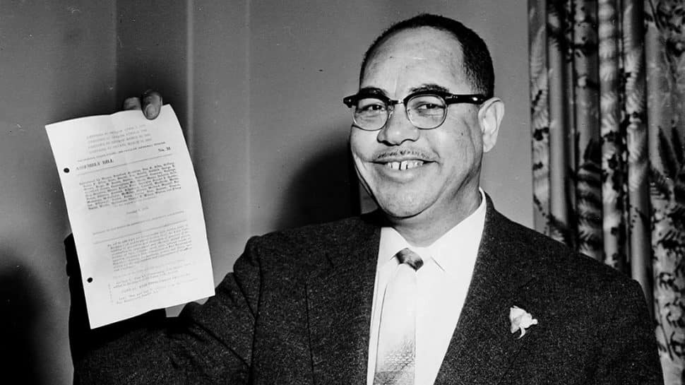 A black-and-white picture shows a black politician holding up a document.