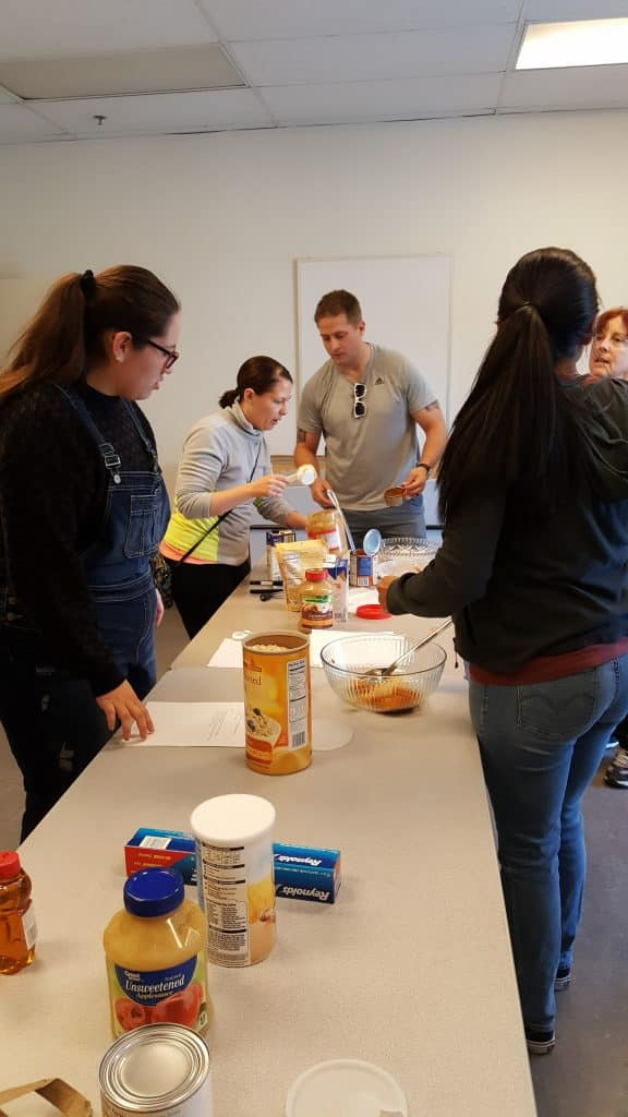 long table with a woman with a ponytial on one side, two volunteers at the end--a woman and a man, and a fourth in front. Jars of peanut butter and dog treats on table. They are making treats for shelter dogs.