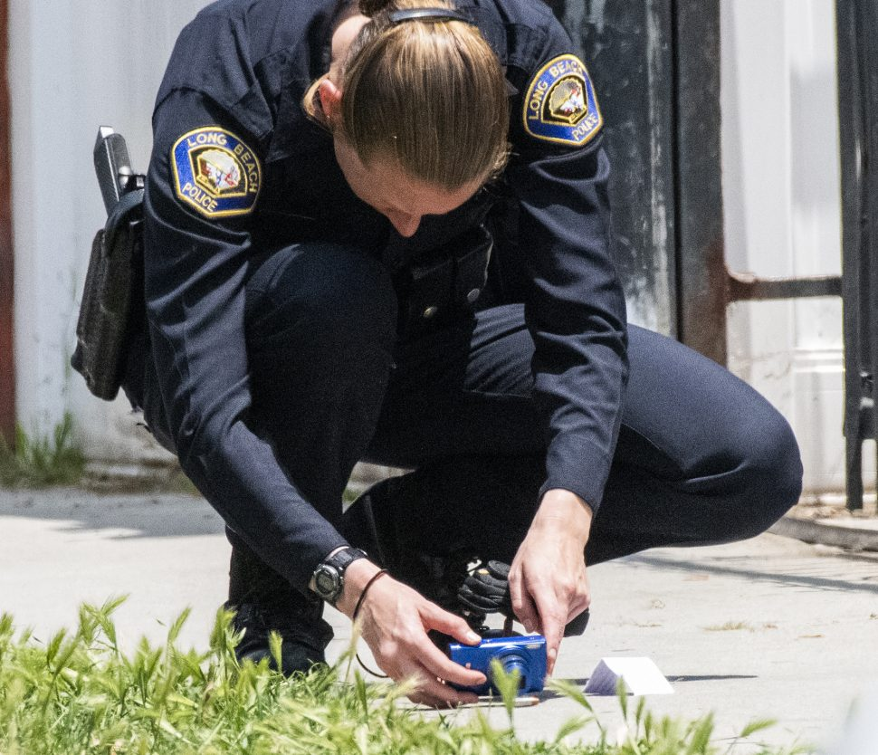 Long Beach police officer takes a photo of a bullet casings as they investigate a shooting where a man was shot and wounded on the 400 block of East 17th Street in Long Beach Friday, May 31, 2019. Photo by Thomas R. Cordova.