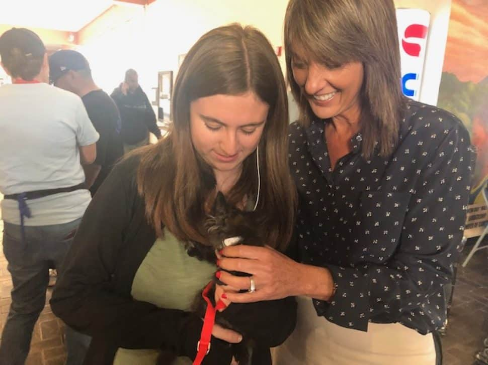 teenage girl with long brown hair with adult woman with long brown hair holding black kitten with red harness, whose head is nuzzled in.
